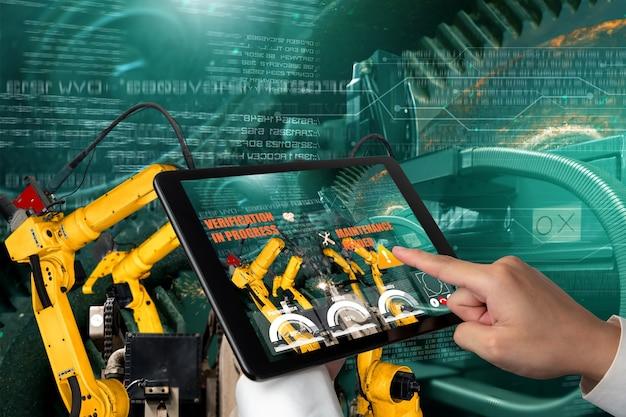 Inżynier kontroluje ramiona robotów za pomocą technologii branży rozszerzonej rzeczywistości
