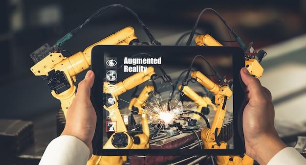 Inżynier kontroluje ramiona robotów za pomocą technologii przemysłowej rozszerzonej rzeczywistości