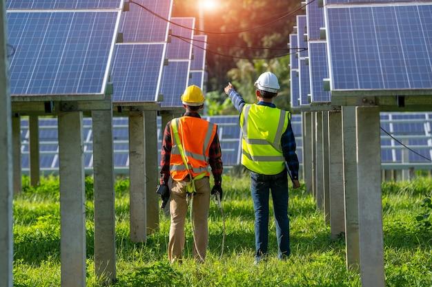 Inżynier lub elektryk pracujący nad wymianą panelu słonecznego w elektrowni słonecznej, koncepcja elektrowni słonecznej do innowacji zielonej energii na całe życie.