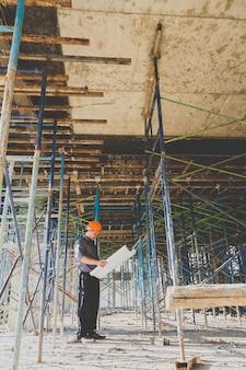 Inżynier lub majster z blueprint w budowie budynku