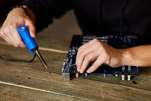Inżynier lub technik naprawia płytkę elektroniczną za pomocą lutownicy.