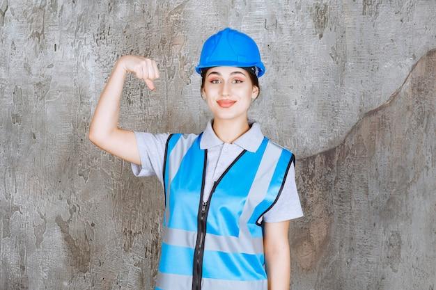 Inżynier ma na sobie niebieski hełm i sprzęt i pokazuje jej mięśnie ramienia.
