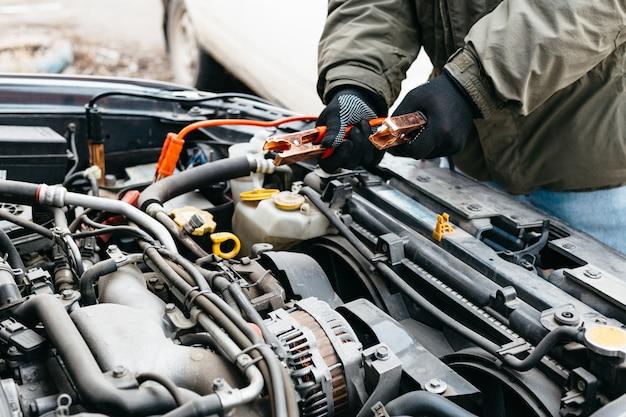 Inżynier mechanik ładujący akumulator samochodowy za pomocą kabli rozruchowych na zewnątrz