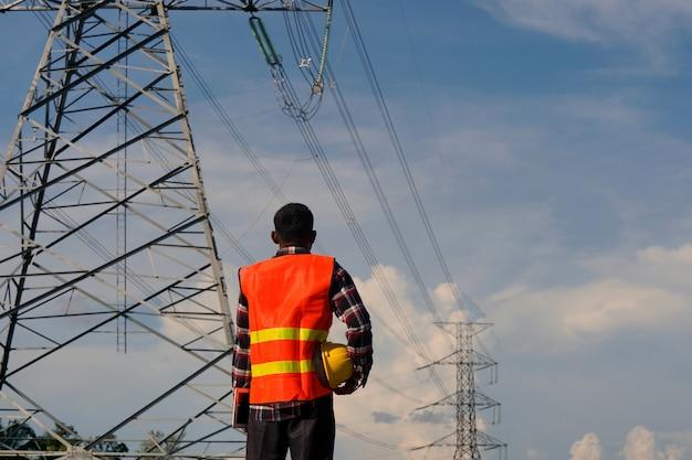 Inżynier mężczyzna korzysta z laptopa i dokonuje inspekcji prac budowlanych. duży słup elektryczny przed placem budowy.