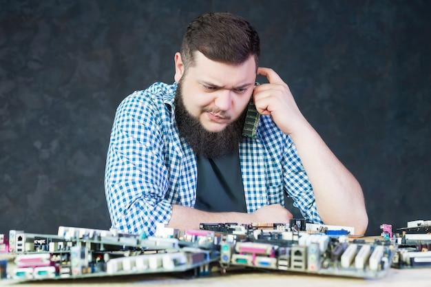 Inżynier mężczyzna pracuje z uszkodzoną płytą główną komputera. technologia naprawy urządzeń elektronicznych