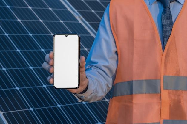 Inżynier, mężczyzna trzyma telefon komórkowy, smartfon na tle paneli słonecznych