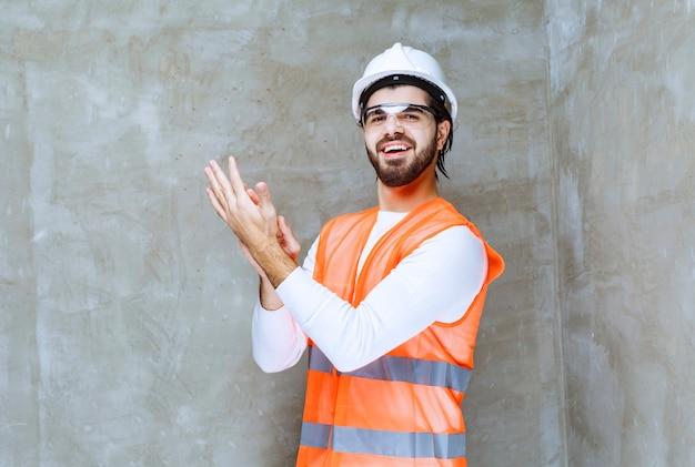 Inżynier mężczyzna w białym hełmie i okularach ochronnych, oklaskiwany przemówieniem.