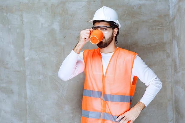 Inżynier mężczyzna w białym hełmie pije z pomarańczowego kubka.