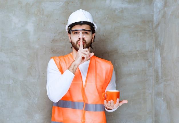 Inżynier mężczyzna w białym hełmie, trzymając pomarańczowy kubek i prosząc o telefon.