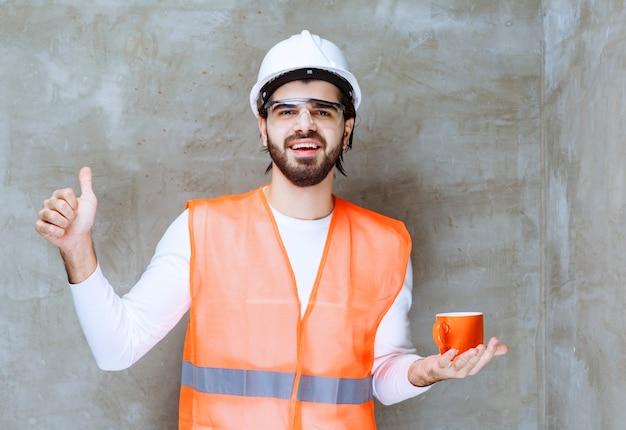 Inżynier mężczyzna w białym hełmie trzymający pomarańczowy kubek i cieszący się smakiem napoju.