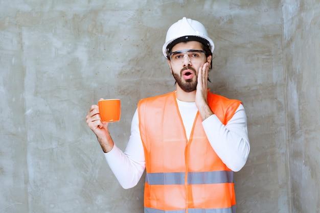 Inżynier mężczyzna w białym hełmie trzymający pomarańczowy kubek i wygląda na zdezorientowanego.