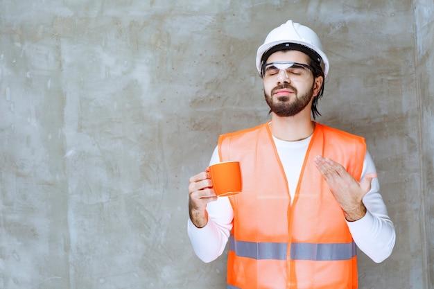 Inżynier mężczyzna w białym hełmie trzymający pomarańczowy kubek.