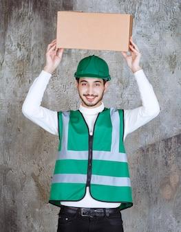 Inżynier mężczyzna w żółtym mundurze i hełmie trzymający kartonową paczkę.