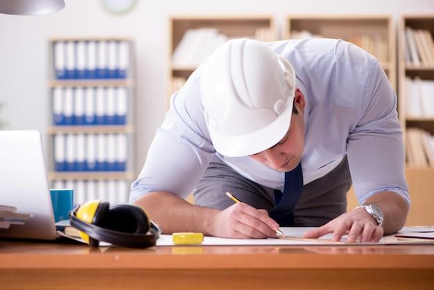 Inżynier nadzorca pracujący nad rysunkami w biurze