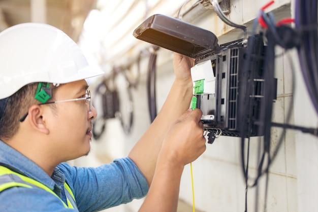 Inżynier naprawy złącza włókien na zbliżeniu tacy rozdzielacza na zewnątrz