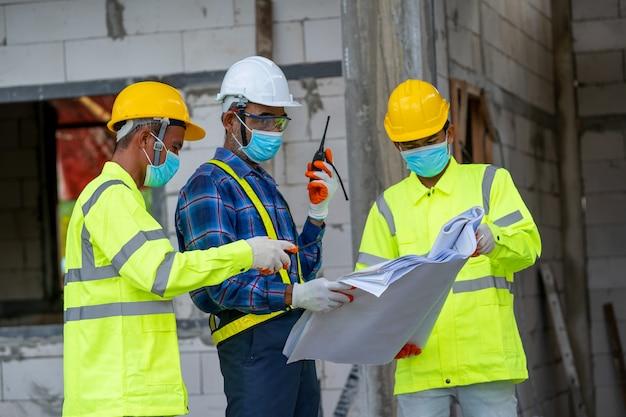 Inżynier noszący maskę i hełm ochronny sprawdzający budynek