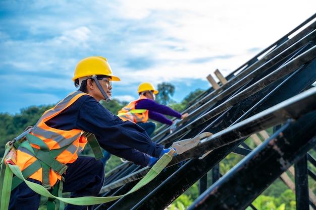 Inżynier noszący szelki bezpieczeństwa i linkę bezpieczeństwa pracujący na wysokim miejscu na placach budowy, narzędzia inżynierskie i koncepcja budowy.