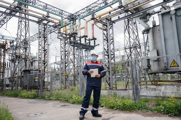 Inżynier podstacji elektrycznej sprawdza nowoczesny sprzęt wysokonapięciowy w masce w momencie wystąpienia blizny. energia. przemysł.
