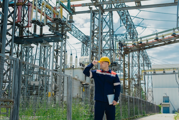 Inżynier podstacji elektrycznej wykonuje prace na sprzęcie wysokiego napięcia.