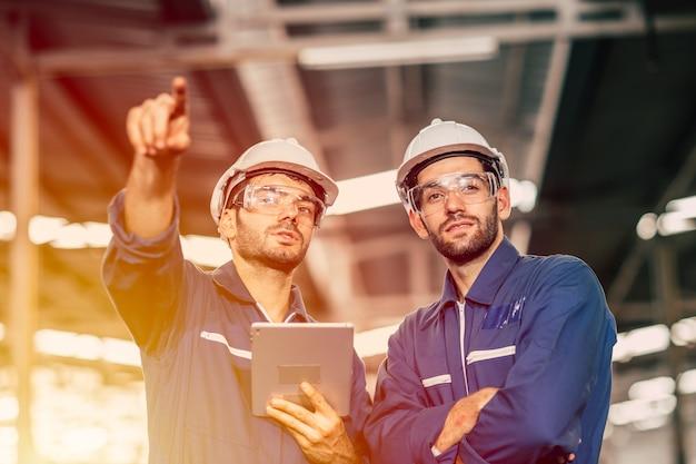 Inżynier pracownik przyjaciel ludzie praca zespołowa dyskusja pomagają we wspólnym wsparciu w pracy w fabryce przemysłu ciężkiego.