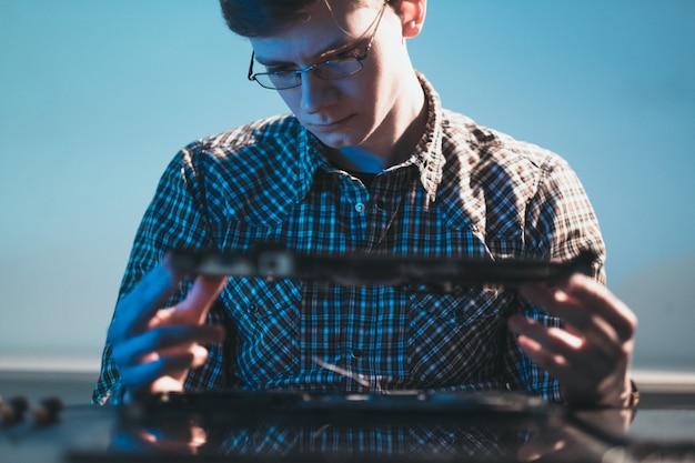 Inżynier pracujący na zdemontowanym laptopie