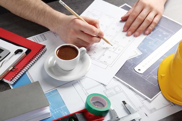 Inżynier pracujący przy stole z rysunkami