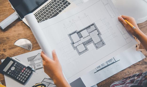 Inżynier pracujący w biurze z planami, inspekcja w miejscu pracy pod kątem planu architektonicznego, projektu budowlanego, budowy firmy
