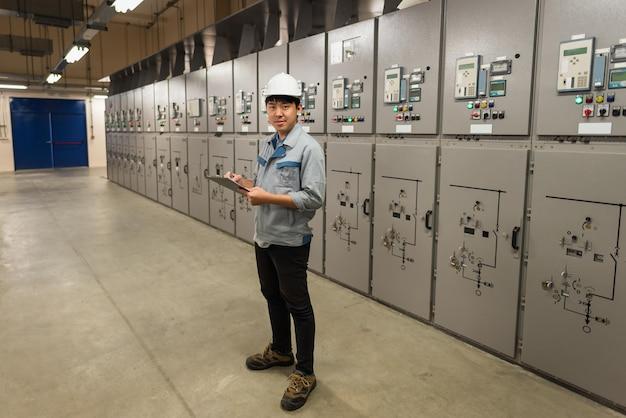 Inżynier pracuje i sprawdza stan rozdzielnicy energii elektrycznej rozdzielni w pomieszczeniu podstacji