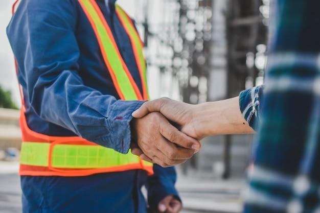 Inżynier pracy zespołowej uścisnąć dłoń na tle budowy witryny