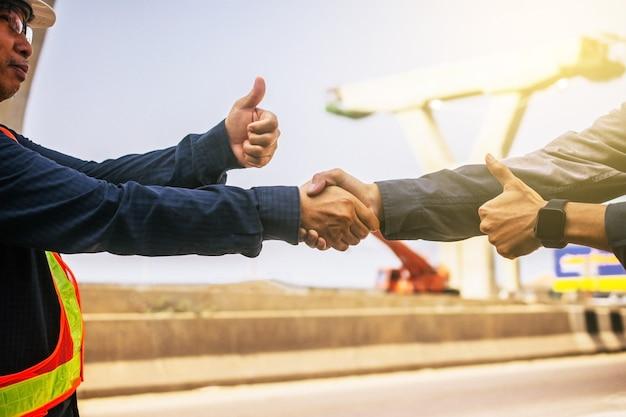 Inżynier pracy zespołowej uścisnąć dłoń sukces architekt budowlany projekt budowlany
