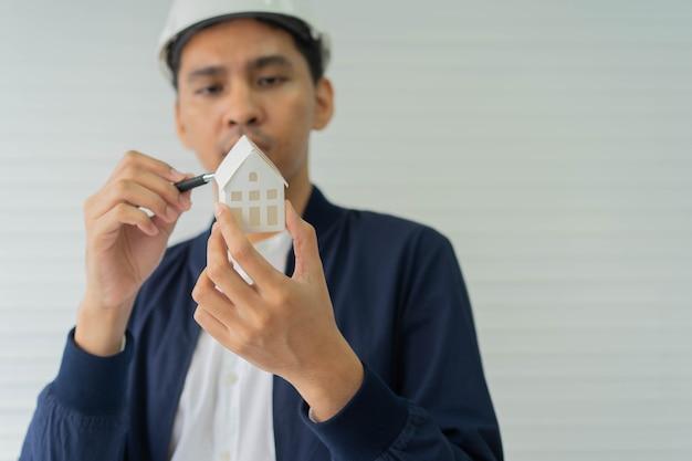 Inżynier ręka trzyma model domu do pomiaru nieruchomości mieszkaniowych i projektu budynków