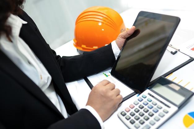 Inżynier rozliczanie projektu pracy z kaskiem w biurze.