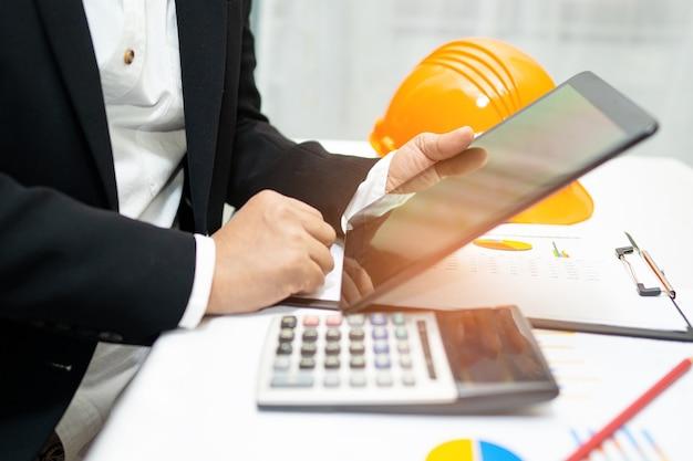 Inżynier rozliczanie projektu roboczego z wykresem i hełmem konstrukcyjnym w biurze.