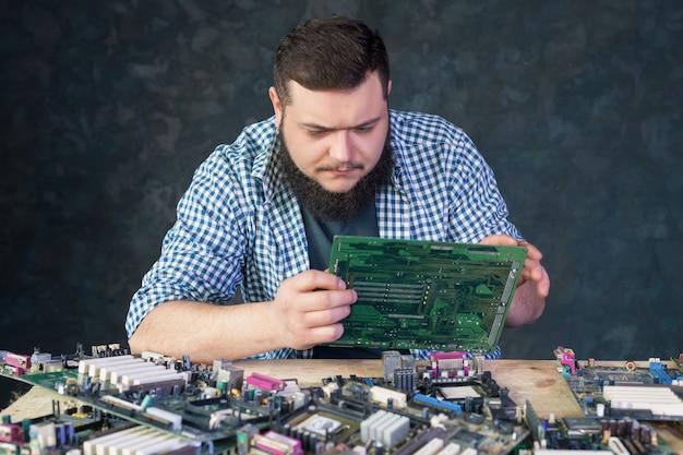Inżynier serwisu pracuje z uszkodzonym sprzętem komputerowym. technologia naprawy elektronicznych podzespołów komputerowych