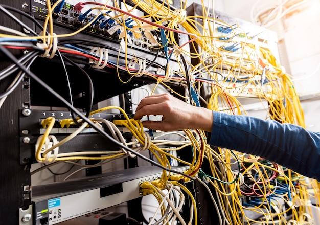 Inżynier sieci pracuje w serwerowni. podłączanie kabli sieciowych do przełączników