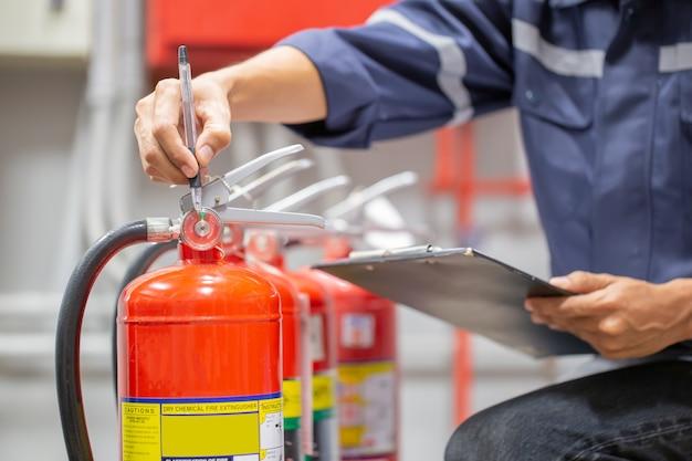 Inżynier sprawdza i sprawdza zbiornik gaśnic w pomieszczeniu kontroli przeciwpożarowej w celu przeprowadzenia szkoleń z zakresu bezpieczeństwa i zapobiegania pożarom.