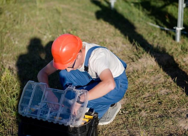 Inżynier sprawdza jego skrzynkę z narzędziami.