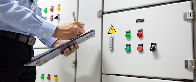 Inżynier sprawdzający centralę wentylacyjną przycisk rozrusznika centrali klimatyzacyjnej w układzie centrali.
