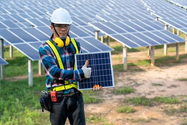 Inżynier sprawdzający panel słoneczny podczas rutynowej pracy w elektrowni słonecznej, w elektrowni słonecznej pod kątem innowacji zielonej energii w celu dostosowania życia.