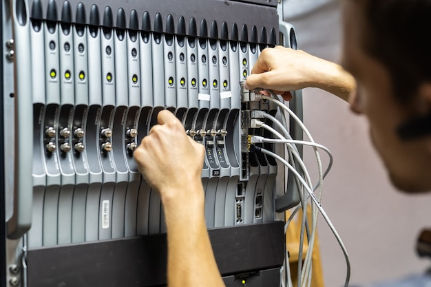 Inżynier technik naprawiający problem z serwerami i danymi w pomieszczeniu kablowym