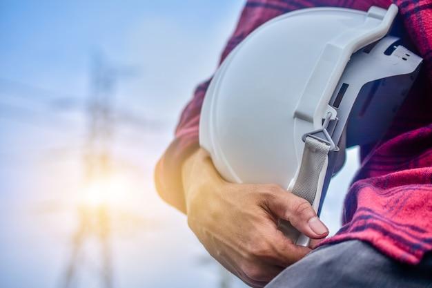 Inżynier trzyma hard hat osoby kierownika usługi wysokiego napięcia elektrowni tło