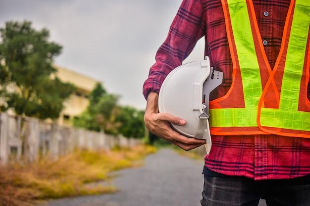 Inżynier, trzymając kapelusz bezpieczeństwa w miejscu pracy