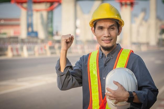 Inżynier trzymający kask na miejscu budowa dróg przy opracowywaniu nowoczesnych systemów transportowych pracownik techniczny zajmuje się przede wszystkim kaskiem ochronnym
