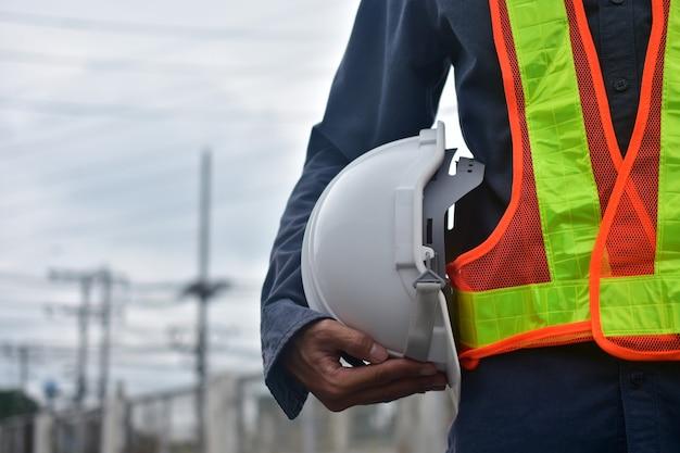 Inżynier trzymający kask ochronny w miejscu pracy i osiedle budowlane, wykonawca architektury ciężkiej, elektryk zawód brygadzista techniczny, profesjonalne użytkowanie bezpieczeństwo inspektora