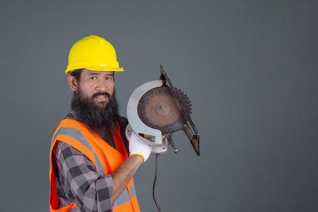Inżynier ubrany w żółty kask z sprzętem budowlanym na szaro.