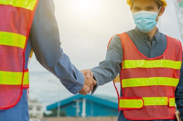 Inżynier uścisk dłoni inżynier zespołu wykonuje pracę na budowie, pracę zespołową w architekturze, uścisk dłoni zespołu