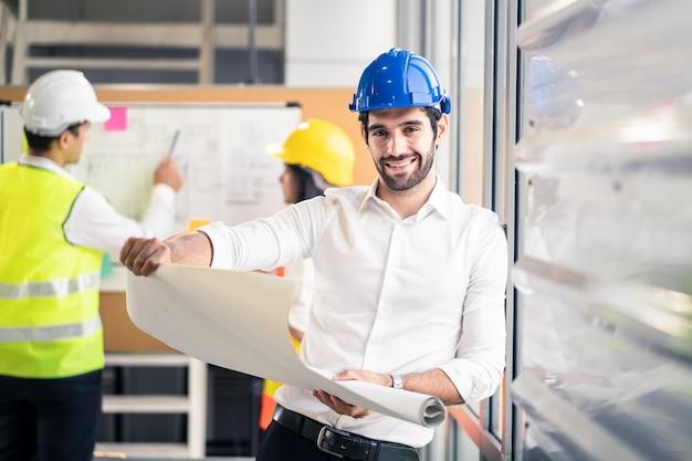 Inżynier uśmiechu kaukaski mężczyzna trzyma rysunek planu, podczas gdy członkowie zespołu udzielają rad burzy mózgów na temat kontroli struktury