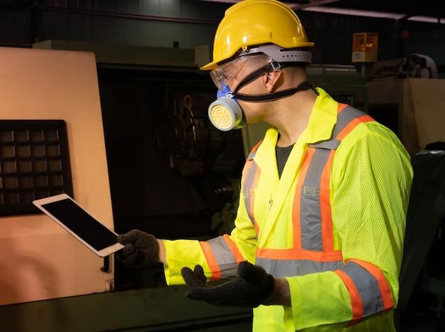 Inżynier używa komputerowej pastylki z ubranym maskę gazową na jego twarzy pracuje w przemysłowej fabryce.