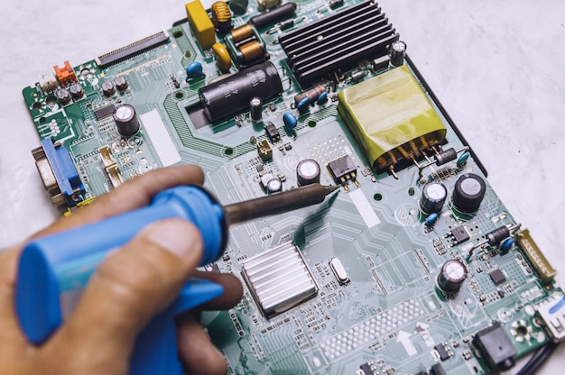 Inżynier używa lutownicy do naprawy płyty telewizyjnej