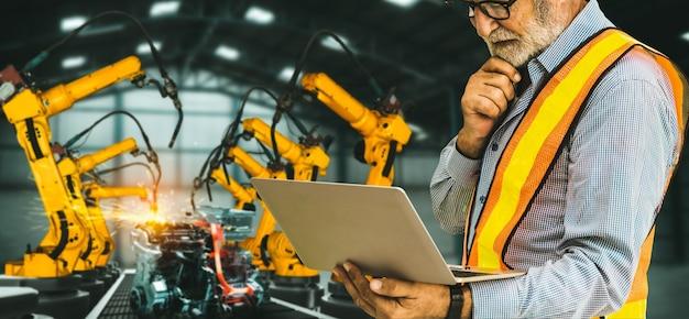 Inżynier używa zaawansowanego oprogramowania zrobotyzowanego do sterowania ramieniem robota przemysłowego w fabryce